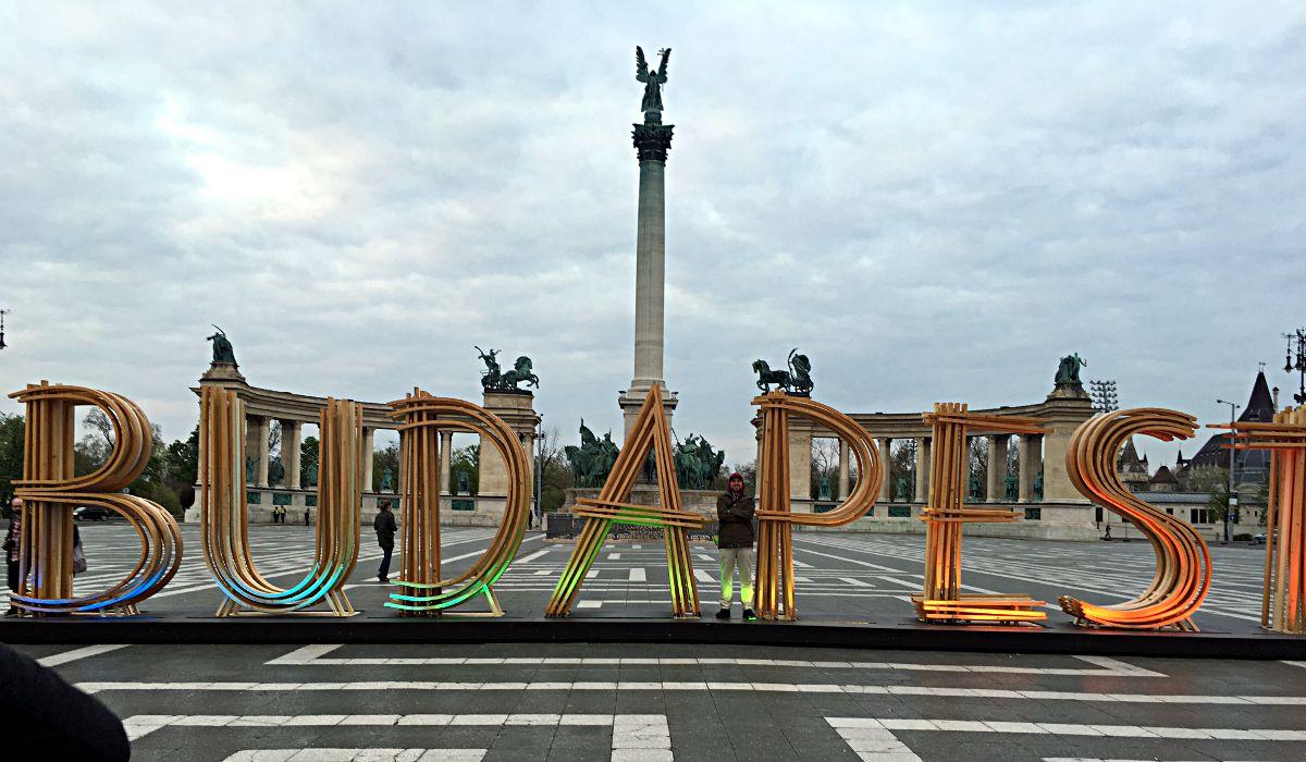 Der antik wirkende Heldenplatz mit seinen mächtigen Statuen und das moderne Kunstwerk mit dem Namen der Stadt ergeben einen bizarren Kontrast, so dass kaum ein Tourist vorbeigeht, ohne ein Foto zu schießen. (Foto: Ruti)