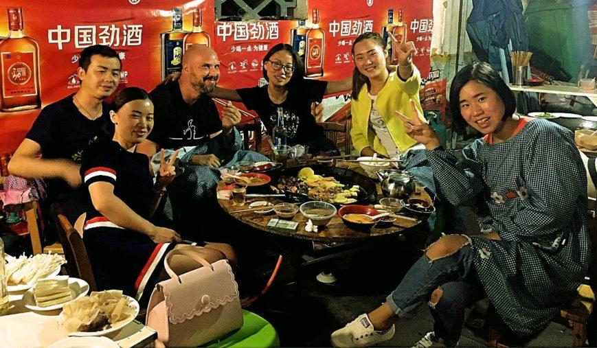 Abendessen mit meinen Freunden aus Liupanshui in China. Weil die Grillpfanne so spritzt, bekommt man Schutzumhänge. Die Dame rechts trägt nicht immer so komische Klamotten. (Foto: Ruti)